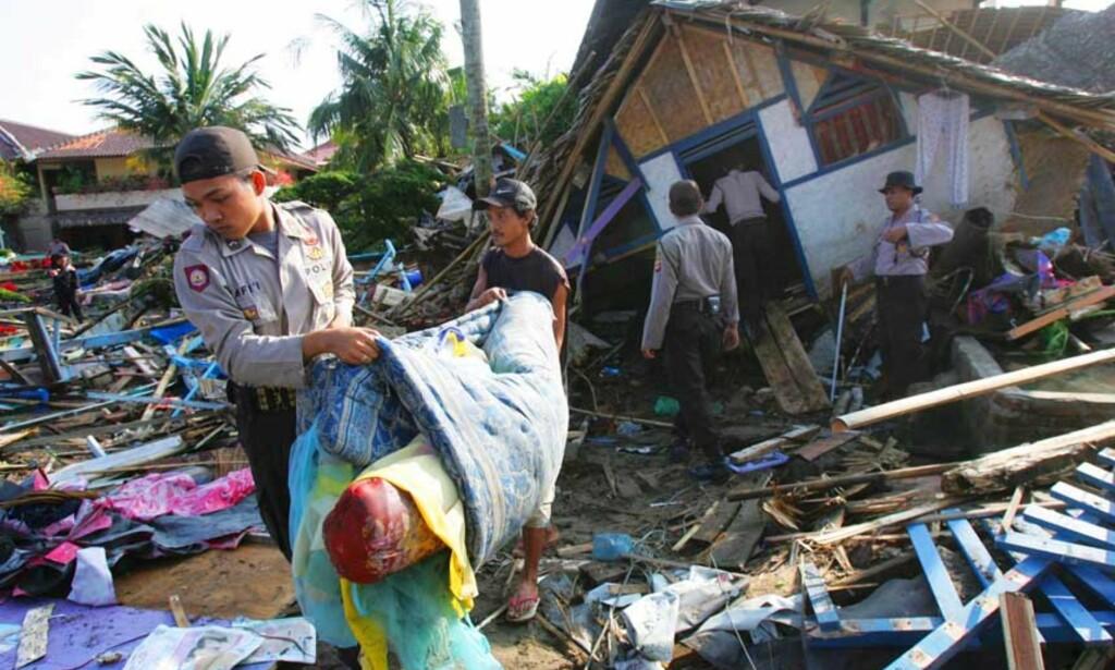 RUINER: Folk rydder i ruinene av hus og bygninger langs stranda. Bølgen gikk 300 meter inn på land. Foto: Scanpix