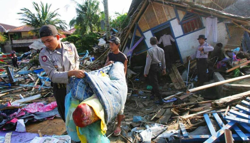 <b>RUINER:</b> Folk rydder i ruinene av hus og bygninger langs stranda. Bølgen gikk 300 meter inn på land. Foto: Scanpix