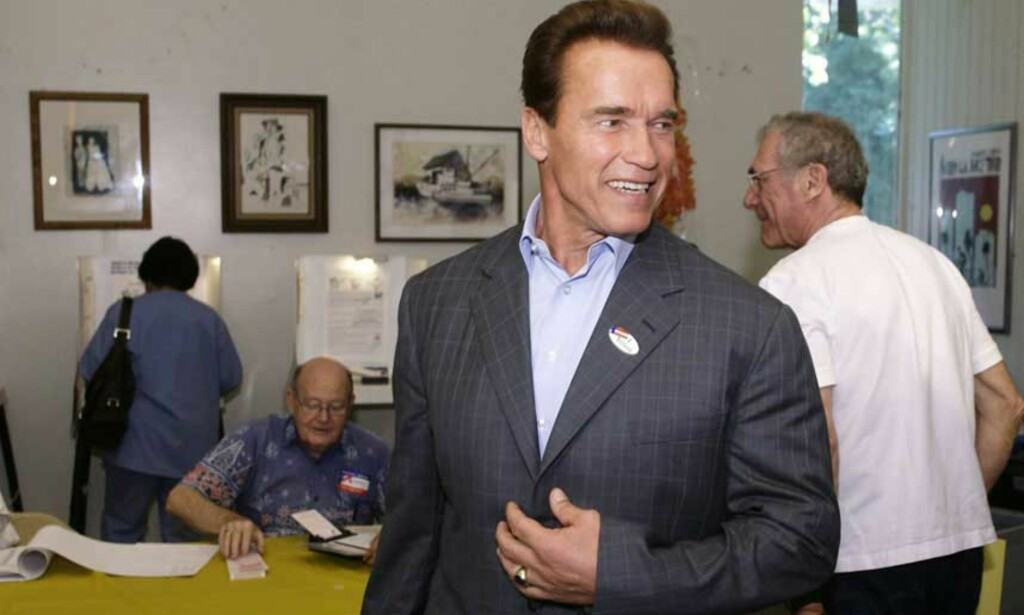 GUVERNØR FOR ANDRE GANG: Arnold Schwarzenegger leder komfortabelt over sin motkandidat, og ligger an til å bli guvernør for andre gang. Her smiler han bredt i stemmelokalet tirsdag. Foto: Reuters/Scanpix
