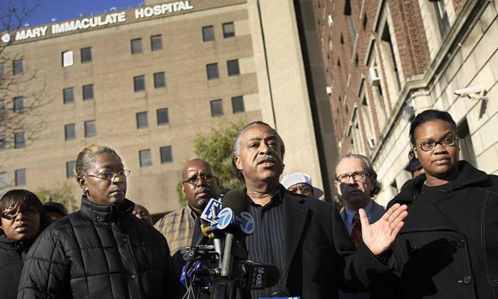 RASENDE: Pastor Al Sharpton (i midten) snakker med pressen utenfor sykehuset hvor to av mennene som ble skutt av politiet befinner seg. Til venstre for ham står moren til Trent Benefeld, til høyre Ebony Guzman, Joseph Guzmans kone. Foto: AP