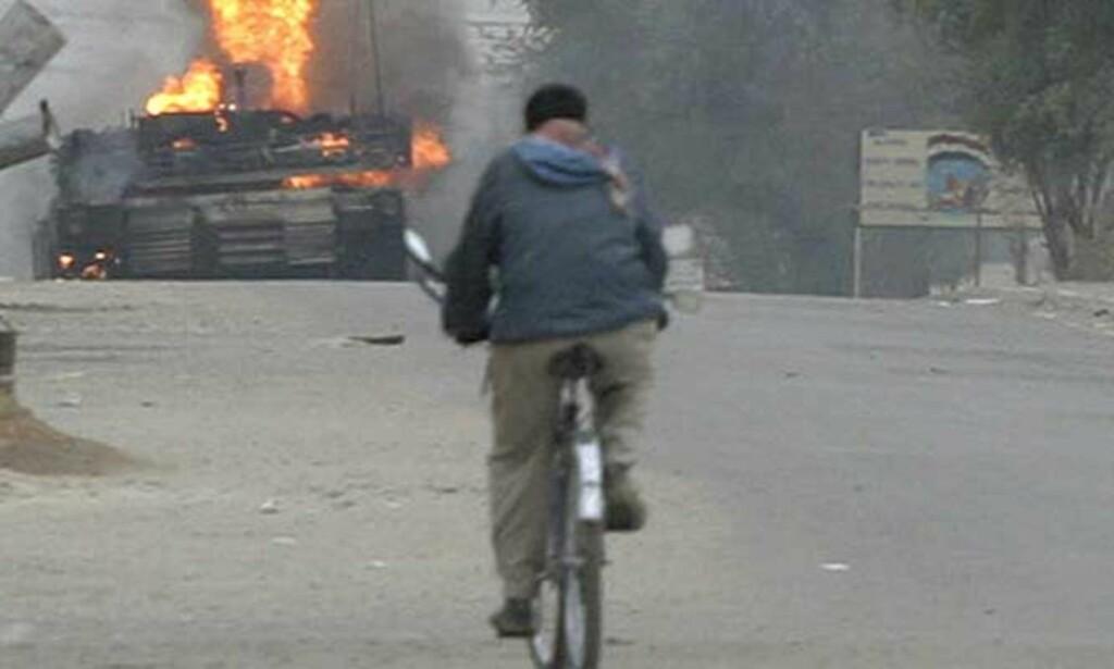 HARDE KAMPER I BAGDAD: Et amerikansk panserkjøretøy brenner etter at det ble rammet av en bombeeksplosjon vest for Bagdad. Tirsdag ble det meldt om nye harde kamper i den irakiske hovedstaden, der regjeringsstyrker støttet av amerikanske soldater gikk til ny offensiv mot sunniarabiske opprørere. Foto: SCANPIX/REUTERS