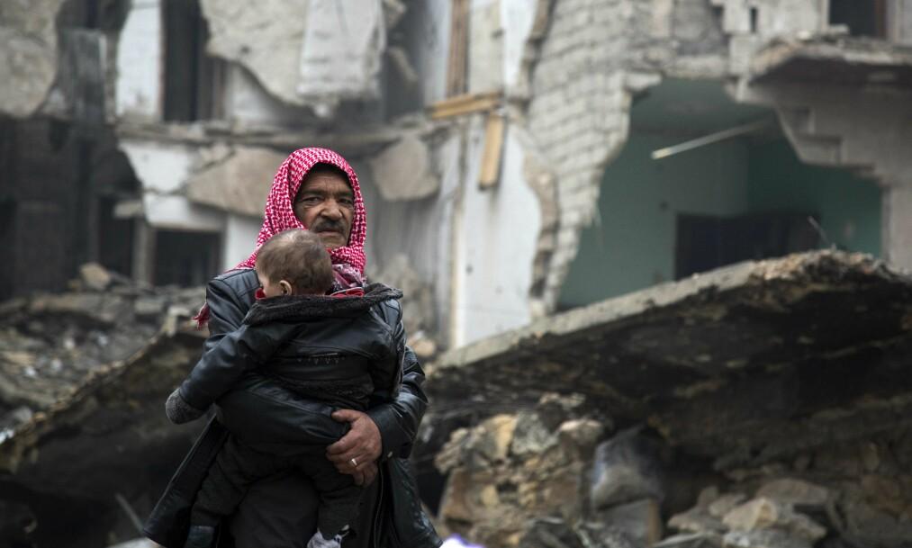 <strong>EN BY I RUINER:</strong> Etter fire år med blodige kamper i Aleppo, er kampen om kontroll over. I går forsøkte sivile å ta seg på flere av bussene som evakuerte folk ut av ruinbyen Aleppo. Foto: AFP Photo / NTB Scanpix