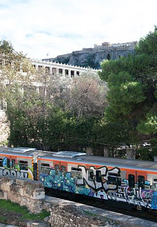 FORTID OG NÅTID: Metroen i Aten er dekorert med fargerik bobleskrift. I bakgrunnen ruver Akropolis over byen.Foto: Marianne Wie