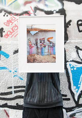 NY DRAKT: Gatekunsten i Aten begynner å finne nye veier. Gatekunstneren NAR (Iakovos Volkov) viser frem foto av installasjonen «Lies» som er del av et større prosjekt med tittel «Can't forget the beautiful lies that you said». Foto: Marianne Wie