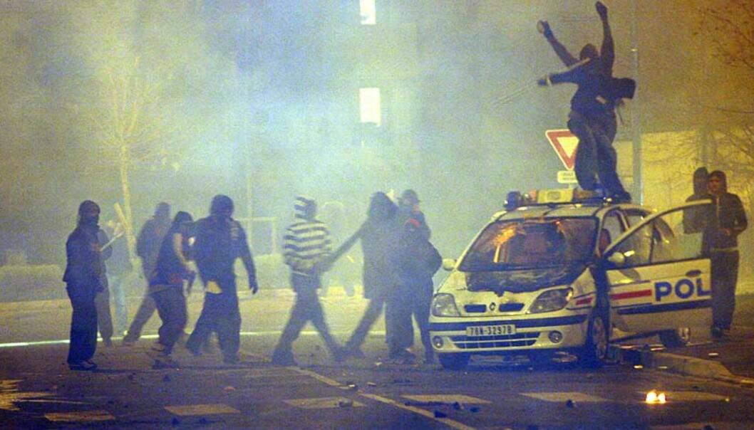 <strong><b>OPPTØYER:</strong></b> Ungdommer i forstaden Villiers-le-Bel nord for Paris ramponerer en politibil. Sammenstøtene søndag og mandag kveld kommer etter at to ungdommer ble drept i en trafikkulykke med en politibil. Foto: SCANPIX/AP/Thibault Camus