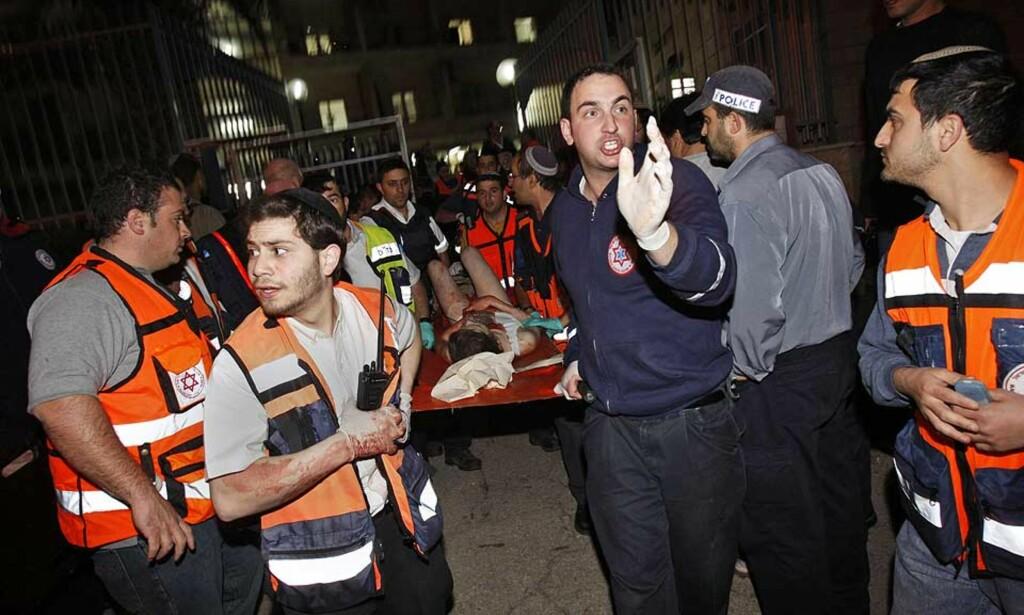 SJU DREPT, MANGE SKADD: Ambulansepersonell frakter bort en av de skadde. Foto: KEVIN FRAYER/AP/SCANPIX