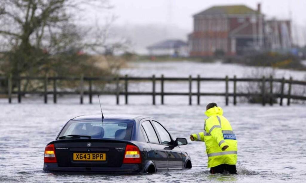 REDDES: En bilist er på dypt vann ved Southampton. Det er meldt flomvarsel over 40 steder og ved kysten regner man med at hus og kaianlegg vil ligge under vann i natt. Foto: CHRIS ISON/AP/SCANPIX