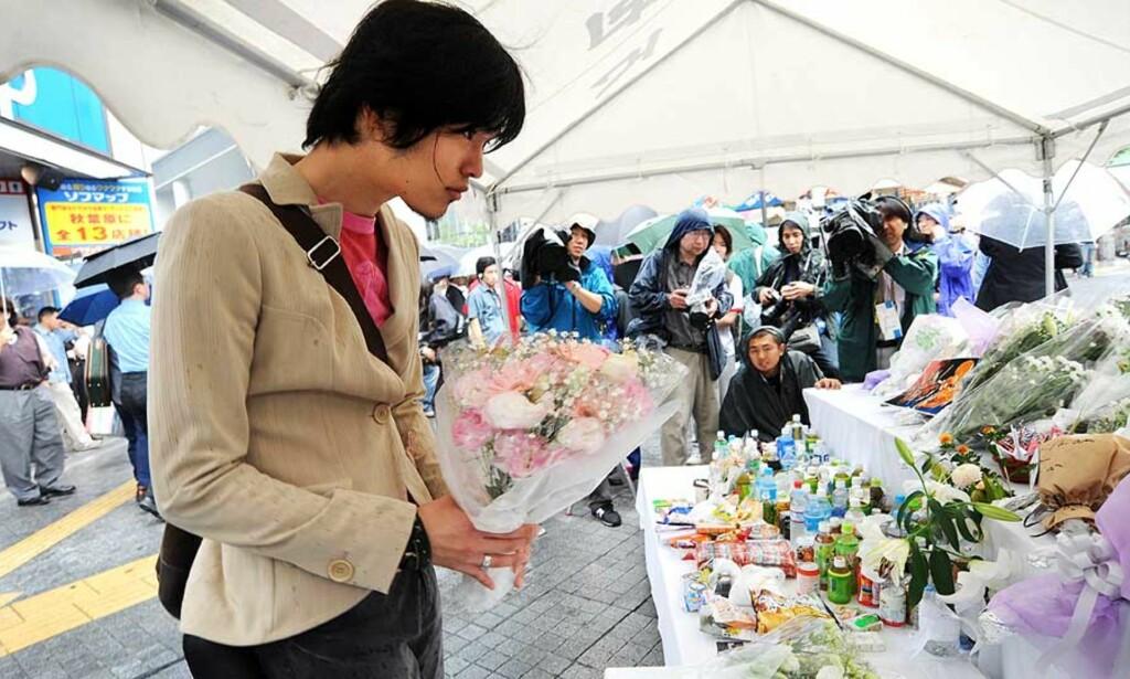 LA NED BLOMSTER: Sørgende legger ned blomster ved åstedet. Foto: Katsumi Kasahara/AP/Scanpix