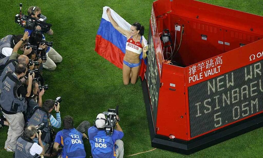 KOSER SEG I FOKUS: Jelena Isinbajeva poserer for fotografene foran resultattavla som viser hennes nye verdensrekord. Foto: AP/SCANPIX