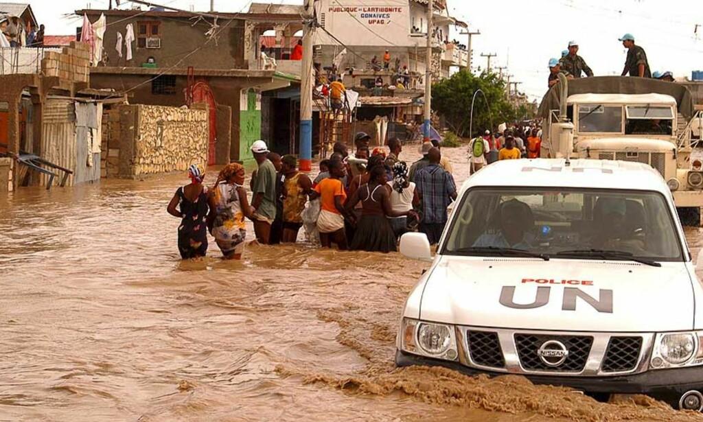 KLARER IKKE HJELPE: Hjelpearbeidere fra FN forsøker forgjeves å hjelpe de flomrammede. Én bil ble skylt av veien på vei inn til Gonaives. Foto: Scanpix