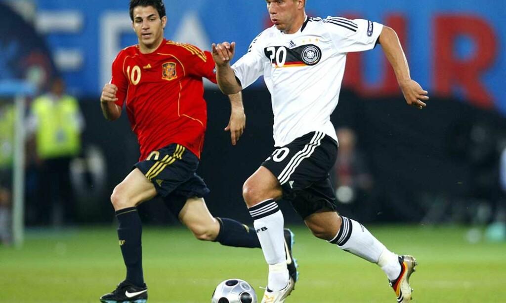ANGRER: Bayern-spissen Lukas Podolski (t.h.) angrer på at han i sin tid signerte for klubben. Lite spilletid skal være grunnen til at han ønsker seg vekk, og han legger ikke skjul på at spill i utlandet er aktuelt. Her under EM-finalen mot Spanias Cesc Fabregas. Foto: Paul Ellis, AFP / SCANPIX