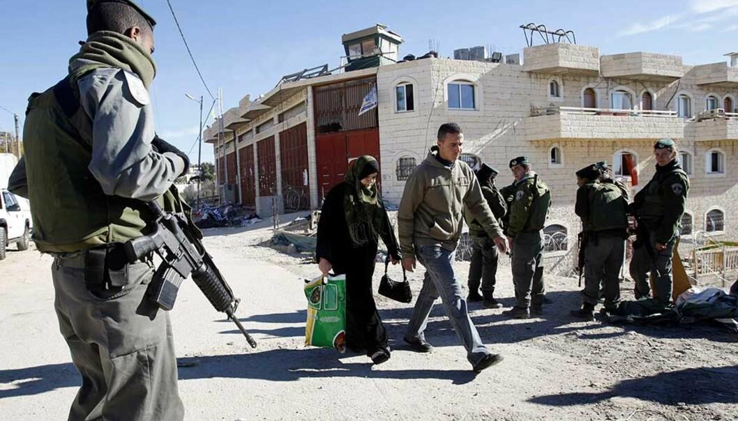 <strong><b>UNDER OPPSYN:</strong></b> En israelsk soldat holder oppsyn med passerende palestinere utenfor huset der 200 jødiske bosettere ble kastet ut med makt i forrige uke. Utkastelsen var direkte motivasjon for skytingen mot tilfeldige palestinere etterpå. Foto: BAZ RATNER/REUTERS/SCANPIX