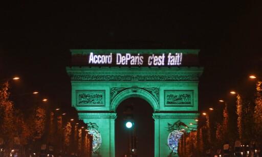 Både Eiffeltårnet og Triumfbuen ble lyst opp med budskapet om at det hadde blitt en enighet om klimaavtale. Foto: Patrick Kovarik / AFP / NTB Scanpix