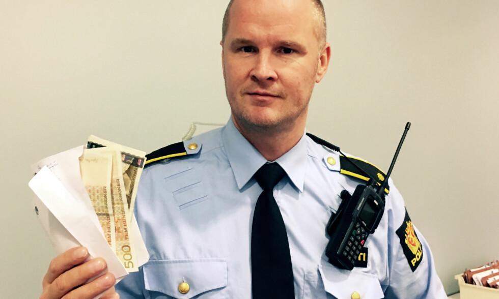 POLITIETS JULENISSE: Vaktleder Rune Valle med mystisk konvolutt og penger. Nå har eieren meldt seg. Foto: Politiet