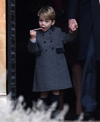 KOSER SEG: Da den britiske kongefamilien var til stede under en julegudstjeneste første juledag, hadde lille George fått en sukkertøystang til å kose seg med. Foto: NTB scanpix