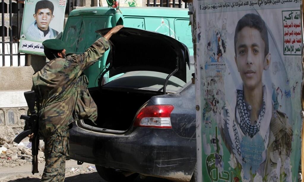 HØYNET SIKKERHET: En mann fra Hutu-militsen undersøker en bil i Sana'a, som er Jemens hovedstad. Rundt ham er bilder av det som skal være avdøde Hutu-krigere.Foto:EPA/YAHYA ARHAB / NTB Scanpix.