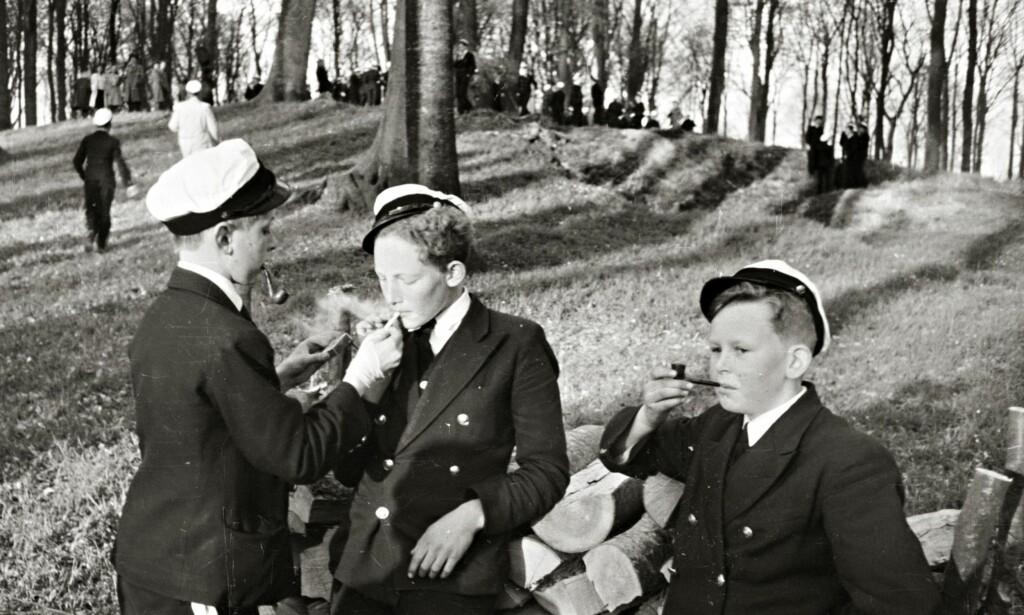GUTTA I RØYKEN: Unge gutter med snadde i kjeften i hine hårde dager. Her ble det nok masse voksenpoeng på en gang, men tidene har forandret seg. Foto: A. E. Andersen / NTB Scanpix