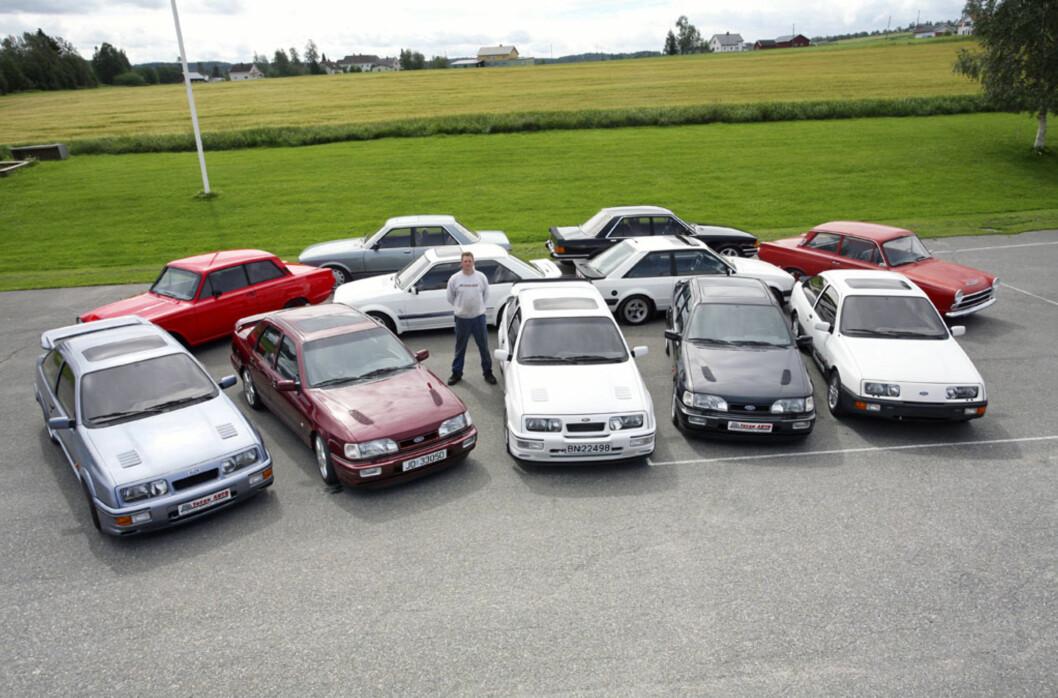 """Her er kremen av Lars Christians samling. Den fremste rekken er kun Ford Sierra Cosworth, med unntak av den til høyre som """"bare"""" er en 2,3. Bak fra venstre ser vi en Cortina 1500, en Granada 2,8i Ghia, en Escort RS Turbo, en Granada 2,3 Jubileum, en Escort XR3i og en Cortina Deluxe. Foto: Lord Arnstein Landsem"""