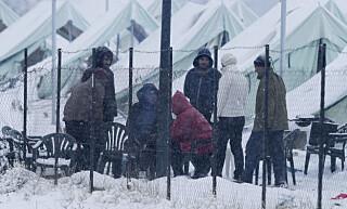 KALDT: Flyktninger som har søkt tilflukt utenfor en ledlagt lagerbygning i Beograd vasker seg ute i kulda 12. januar i år. Grensene som fører videre nordover og vestover i Europa er stengt. Foto: Josep Vecino / Anadolu Agency / NTB Scanpix