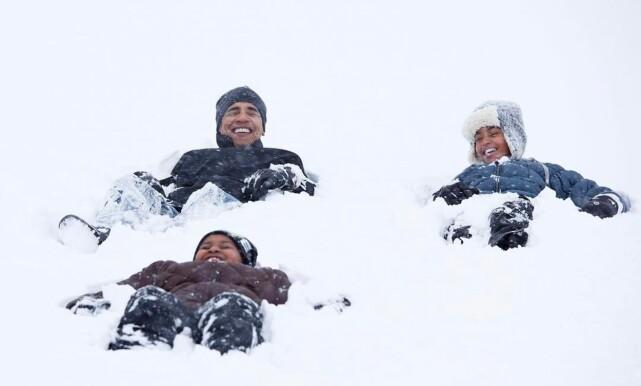 PAPPAS ENGLER: Barack Obama og døtrene lager engler i snøen. Foto: Pete Souza / The White House / NTB Scanpix