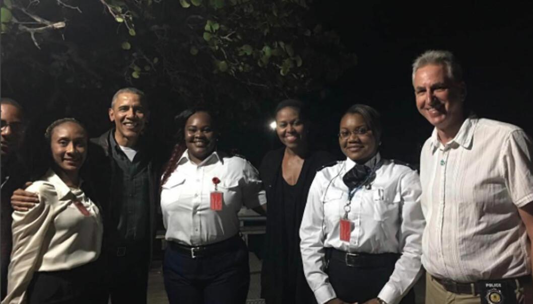 <strong>GODT HUMØR:</strong> Barack og Michelle Obama var i godt humør da de stilte opp for fotografering sammen med funksjonærene i immigrasjonkontrollen på De Britiske Jomfruøyene. Her skal det avgåtte presidentparet nyte luksusen på Richard Bransons private paradisøy. Foto: Facebook / NTB Scanpix &nbsp;