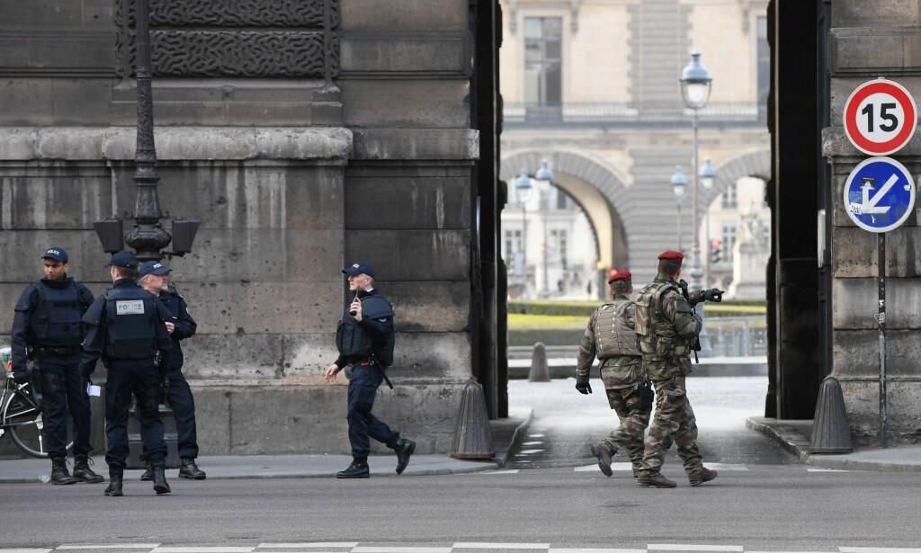 SIKKERHETSSTYRKER: Fransk politi og militærstyrker patruljerer området rundt kunstmuseet Louvre i Paris etter at en mann ble skutt av en soldat fredag. Mannen skal ha forsøkt å angripe den franske soldaten med en machete. Foto: AFP Photo / NTB Scanpix