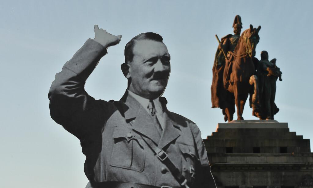 En person utkledd som Hitler har flere ganger dukket opp i diktatorens fødeby. Her en pappfigur av nazilederen som er satt opp i byen Koblenz i Tyskland, for å advare mot fascismens farer. Foto: Torsten Silz /AP / NTB scanpix