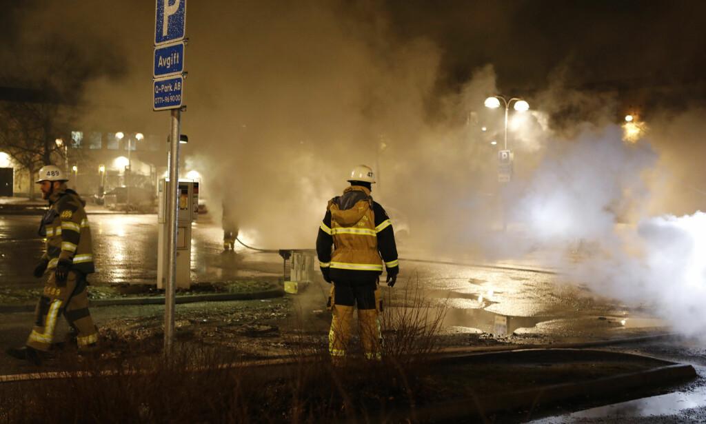 KAOTISK: En politimann er skadd og flere biler skal være utbrent i Stockholm-forstaden Rinkeby. Foto: Christine Olsson / TT / NTB scanpix