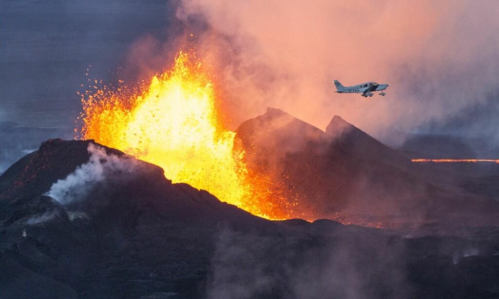 FARETRUENDE NÆR: Dette bildet fra 2014 viser et utbrudd ved vulkanen Bárðarbunga (Bardarbunga) i det et fly våger seg over fjelltoppen. Foto: Bernard Meric / AFP / NTB Scanpix