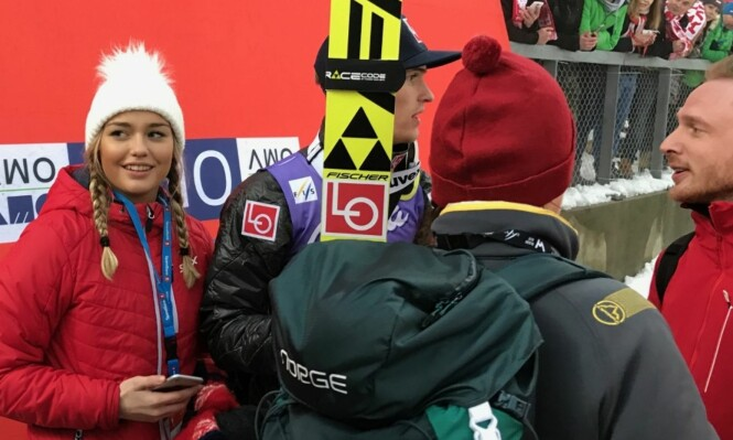 <strong>HYGGELIG MØTE:</strong> Kjæresten Anja Nymoen Søberg (til venstre) møtte Daniel-André Tande med et smil og et kyss på sletta i Holmenkollen etter lagkonkurransen. Her er Tande i prat med NRK-ekspert Johan Remen Evensen (til høyre). FOTO: TORE ULRIK BRATLAND