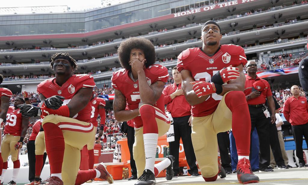 LEDET AN: Den amerikanske fotballspilleren Colin Kaepernick (i midten) ledet an i den stille protesten med å gå ned på kne under nasjonalsangen for å demonstrere mot rasisme og politivold. Her er han med lagkameratene i San Francisco 49ers, Eli Harold og Eric Reid i 2016. Denne protesten fikk massiv oppmerksomhet. Foto: AP Photo/Marcio Jose Sanchez, File