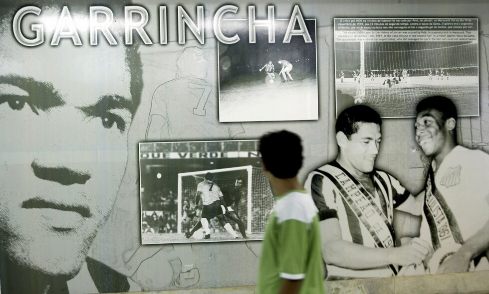 KULTFIGUR: En liten gutt går forbi en utstilling til ære for brasilianske Garrincha på Maracan Stadion i Rio de Janeiro. Garrincha var kontroversiell og blant annet far til 14 barn som han hadde fått med forskjellige kvinner. Han var også alkoholiker. Men på banen var han enestående. Foto: REUTERS/Bruno Domingos/NTB Scanpix