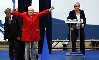(FILES) This file photo taken on May 01, 2015 shows France's far-right political party Front National (FN) founder and honorary president Jean-Marie Le Pen gesturing on stage as FN's president Marine Le Pen looks during the party's annual rally in honour of Jeanne d'Arc (Joan of Arc), in Paris. Front National (National Front - FN) leader Marine Le Pen arrived slightly behind the pro-European centrist candidate with 21.53 percent of the votes in the first round of France's Presidential election on April 23, 2017. / AFP PHOTO / KENZO TRIBOUILLARD