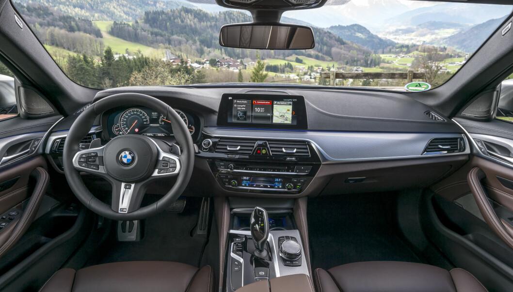 <strong>POTENT:</strong> Det er det velkjente, førerorienterte interiøret fra nyeste generasjon 5-serie - med M-logo nederst på rattet. Foto: BMW