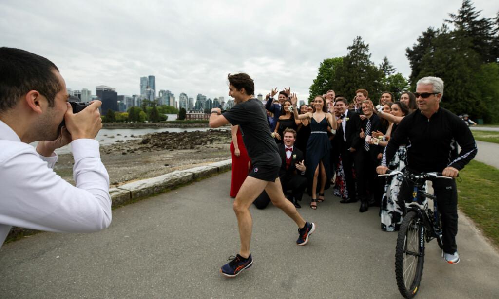 OVERRASKELSE: Statsminister Justin Trudeau (45) var på joggetur da han plutselig «fotobombet» en gruppe med elever som skulle forevige skoleball-kvelden. Foto: NTB Scanpix