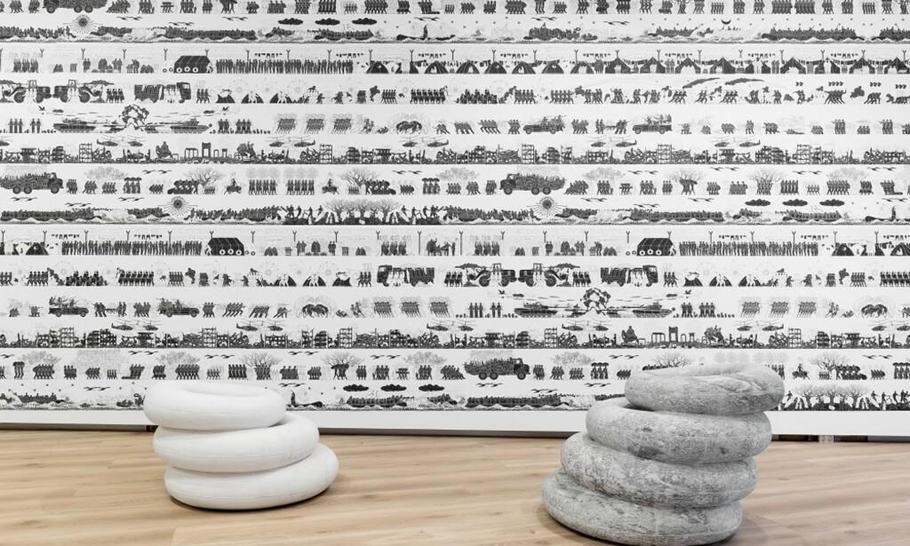 FLYKTNINGKRISE: Ai Weiweis installasjon gjenskaper bildekk brukt som livbøyer av flyktninger som krysser Middelhavet. Rommet er tapetsert med ikoniske friser som viser flyktningenes livssituasjon. Foto: Christian Øen