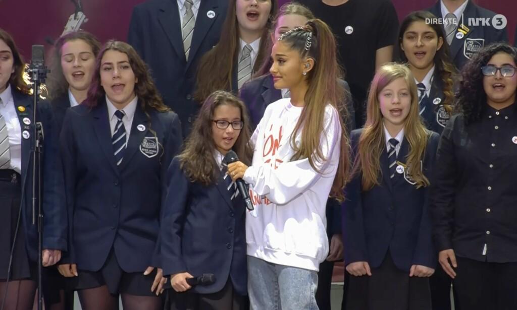 TILBAKE I MANCHESTER: Artist Ariana Grande avbildet i Manchester, der hun søndag kveld opptrer sammen med et stjernelag av artister. Her sammen med en gruppe elever fra Parrs Wood High School i Manchester. Skjermdump: NRK