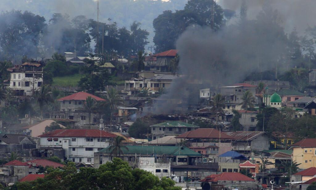 HARDE KAMPER: Dette bildet fra i dag viser røyk fra en bygning i Marawi, der kampene fortsatt raser mellom regjeringsstyrker og krigere fra Maute og Abu Sayyaf. Foto: Romeo Ranoco / Reuters / NTB Scanpix
