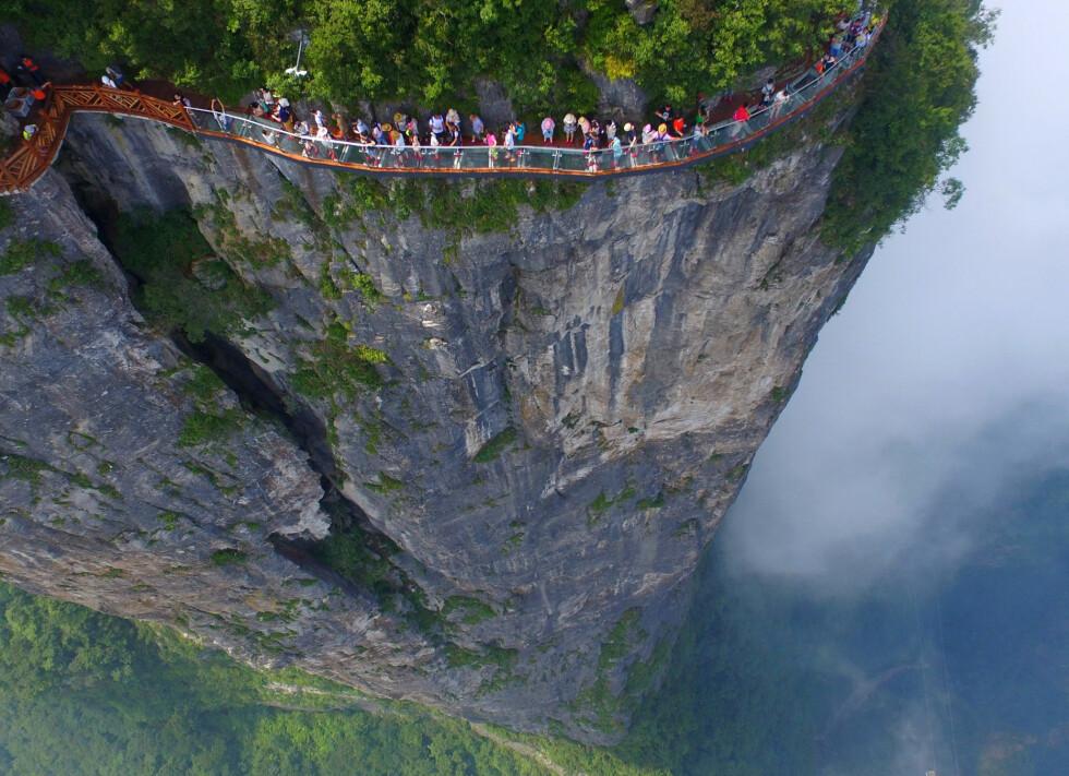 GIKK EN TUR PÅ STIEN: I Hunan-provinsen i Kina kan du gå en sti litt utenom det vanlige. Denne plattform-stien er 1,6 kilometer lang og befinner seg høyt oppe i Tianmen-fjellene, også kalt «porten til himmelen». For å komme deg hit må du ta verdens lengste taubane - 14 kilometer lang. Her får du virkelig testet høydeskrekken. Foto: NTB Scanpix