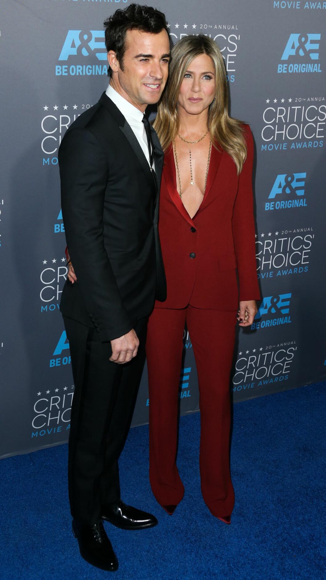 <strong>ALTERNATIVT:</strong> Den todelte dressen trenger ikke være sort eller hvit! Her er Jennifer Aniston med ektemannen Justin Theroux under en filmprisutdeling i Hollywood i januar. Skuespilleren strålte i en dyprød dress med dyp kløft. Foto: NTB Scanpix