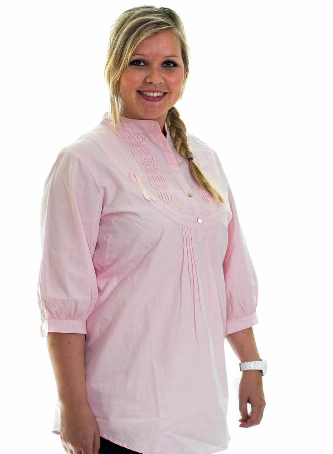 En vid bluse/skjorte, designet av Nora Farah for Rosa sløyfe-aksjonen. Blusen har knapper i halsen og fine detaljer, kr 499. Foto: Tobias Barvik / Kreftforeningen
