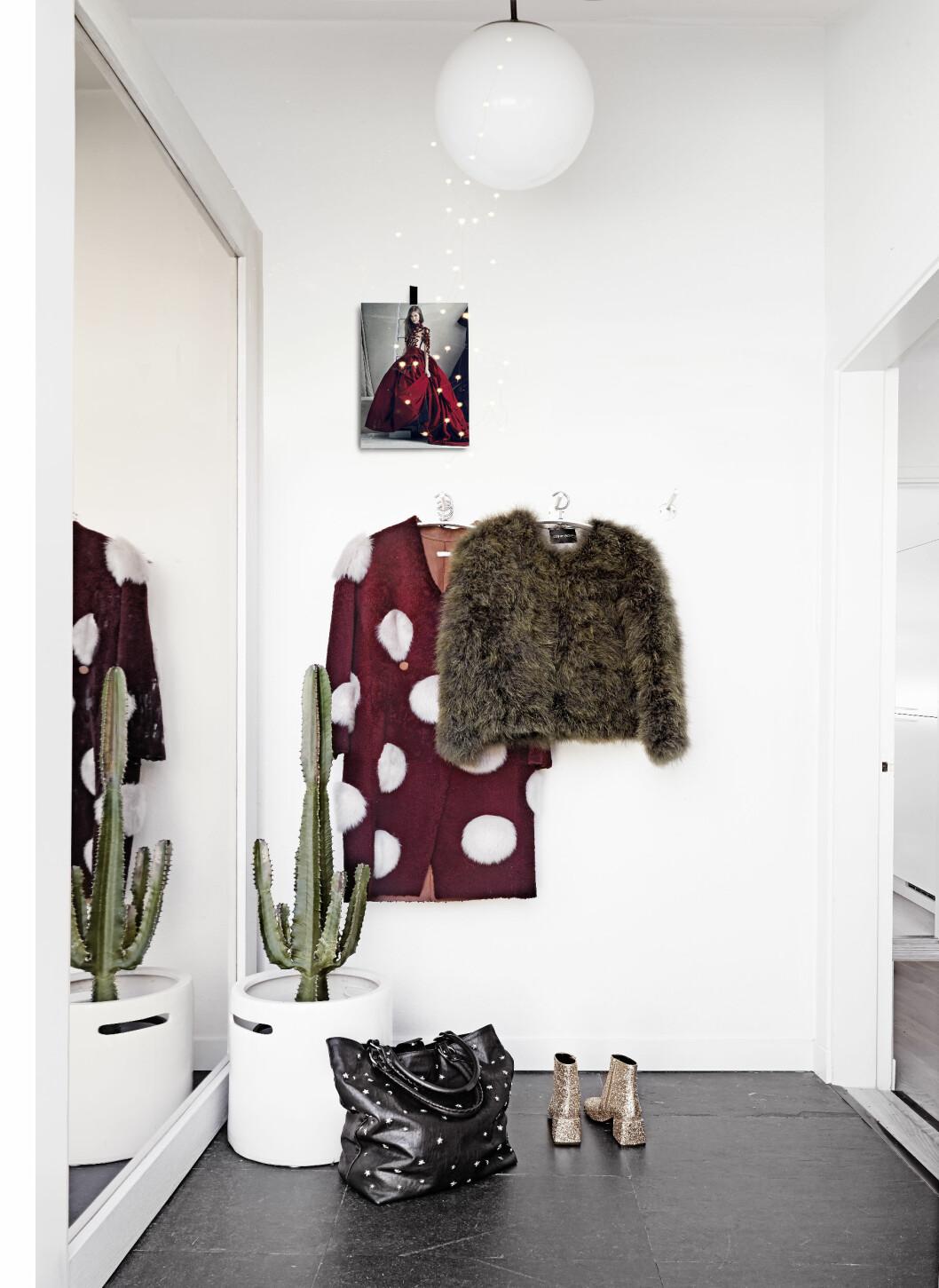 BRUK KLÆR SOM PYNT: Malin får farger inn i det svart-hvite interiøret på en naturlig måte. Den prikkete jakken er fra Anne Vest i København og pelsjakken fra Gemma Shop.  Foto: Sara Svenningrud