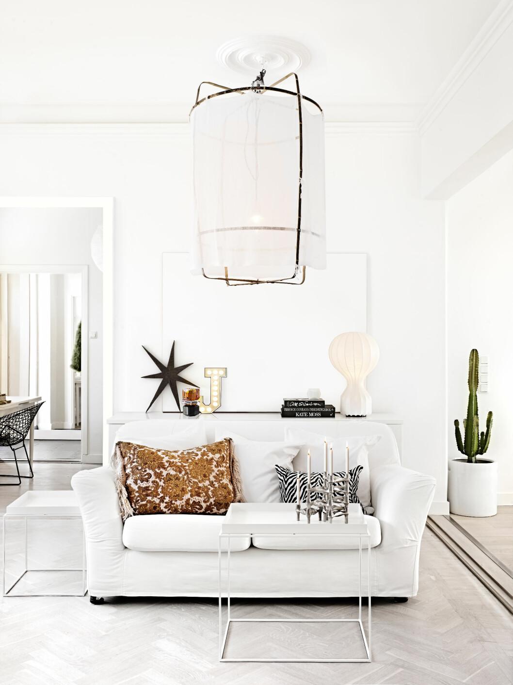 KUL STUE: Taklampen er fra Atrilleriet, sofaen er fra Ikea og putene er hjemmesydde. Lampen på sjenken bak er Gatto Lamp fra Flos.  Foto: Sara Svenningrud