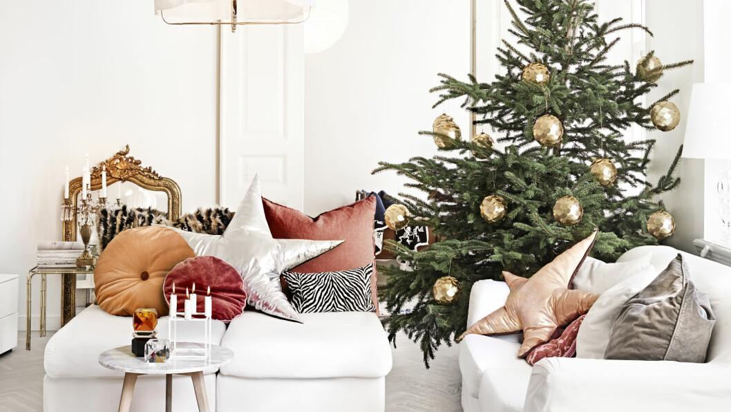UTRADISJONELL JUL: Hjemme hos Malin og familien finner du ikke mange nisser. Her er det derimot tatt i bruk en konjakkfarge som er en herlig og varm variant til klassisk julerødt. Sofaen er fra Ikea, speilet fra lauritz.com og putene er hjemmesydde.  Foto: Sara Svenningrud