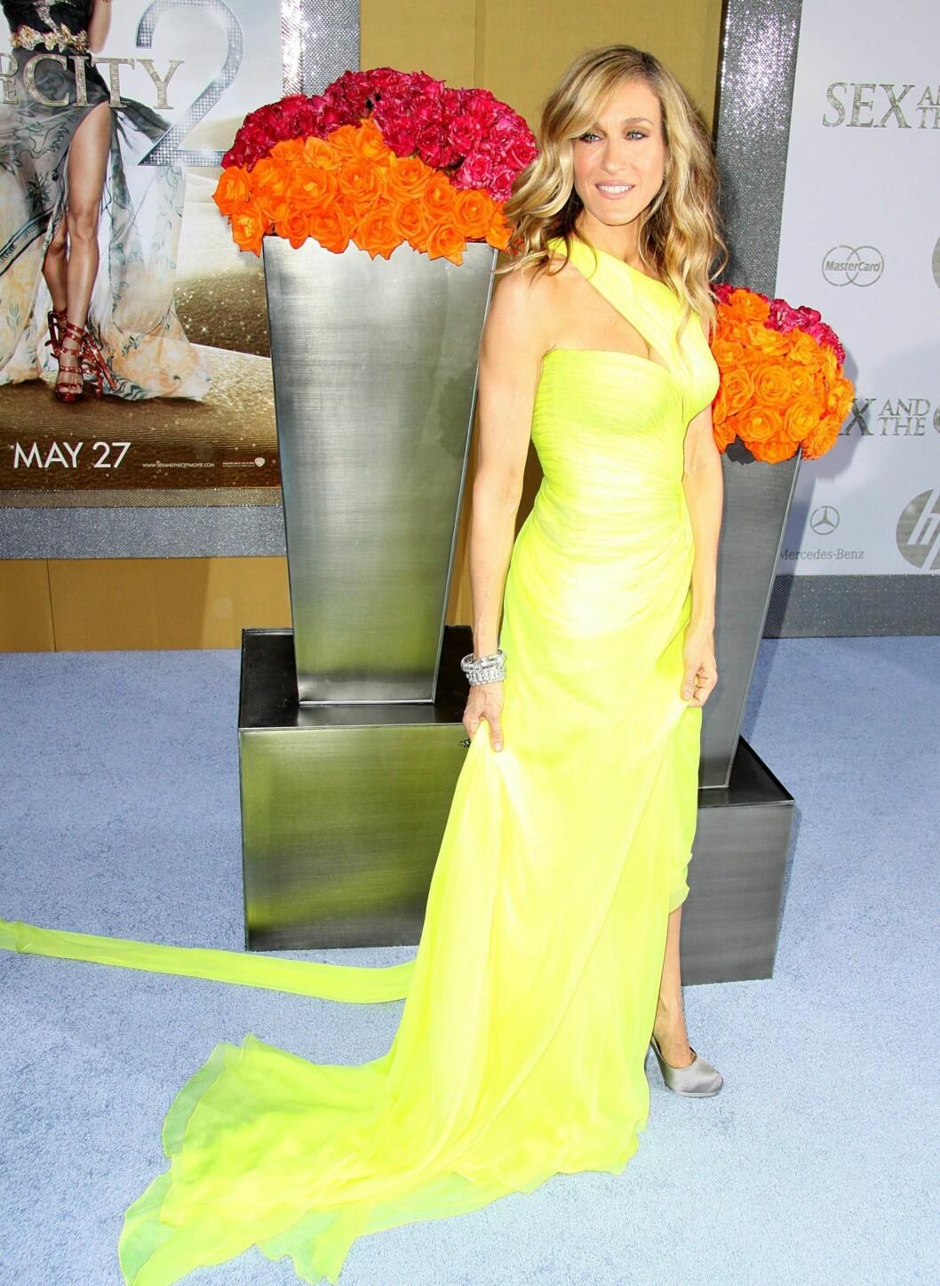Sarah Jessica Parker spiller hovedrollen som Carrie Bradshaw, i neongul kjole med slep og splitt.  Foto: All Over Press
