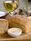 Freshly baked crusty herb bread on wooden board with aioli garlic mayonnaise and a glass of white wine Foto: All Over Press