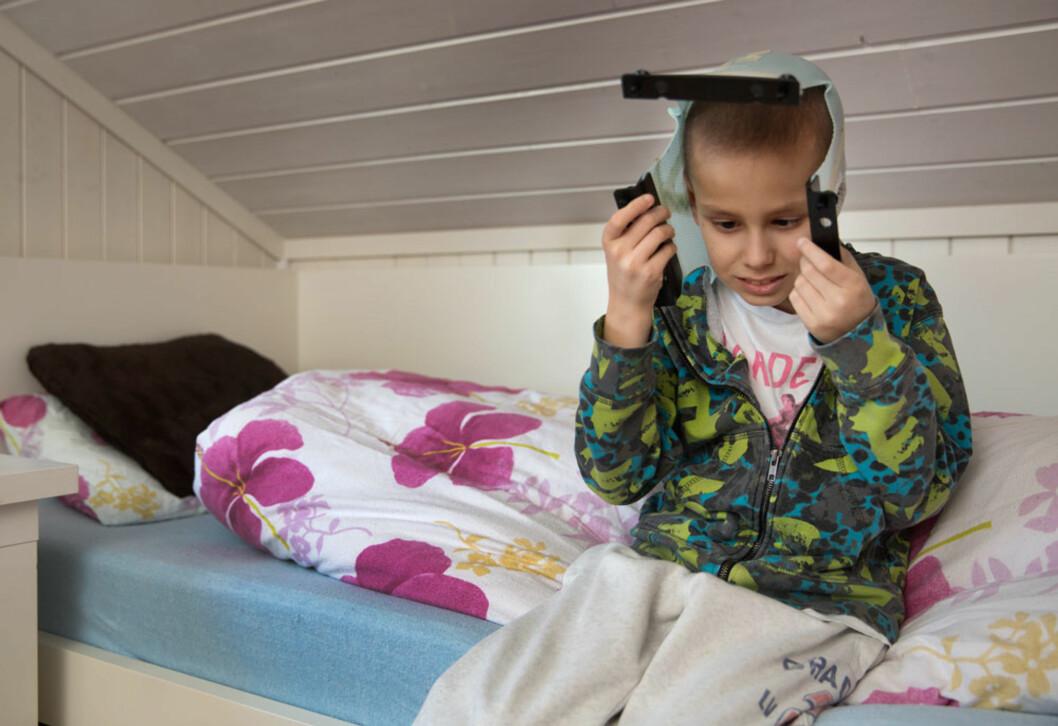 STRÅLING: Adrian jubler over at han er erklært frisk, mens han stolt viser fram hjelmen han hadde på når han fikk strålebehandling. Foto: Sverre Jarild