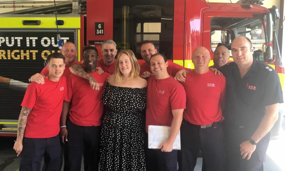 OVERRASKET: Adele overrasket en rekke brannmenn på Chelsea brannstasjon da hun dukket opp med kaker. Foto: AP / NTB Scanpix
