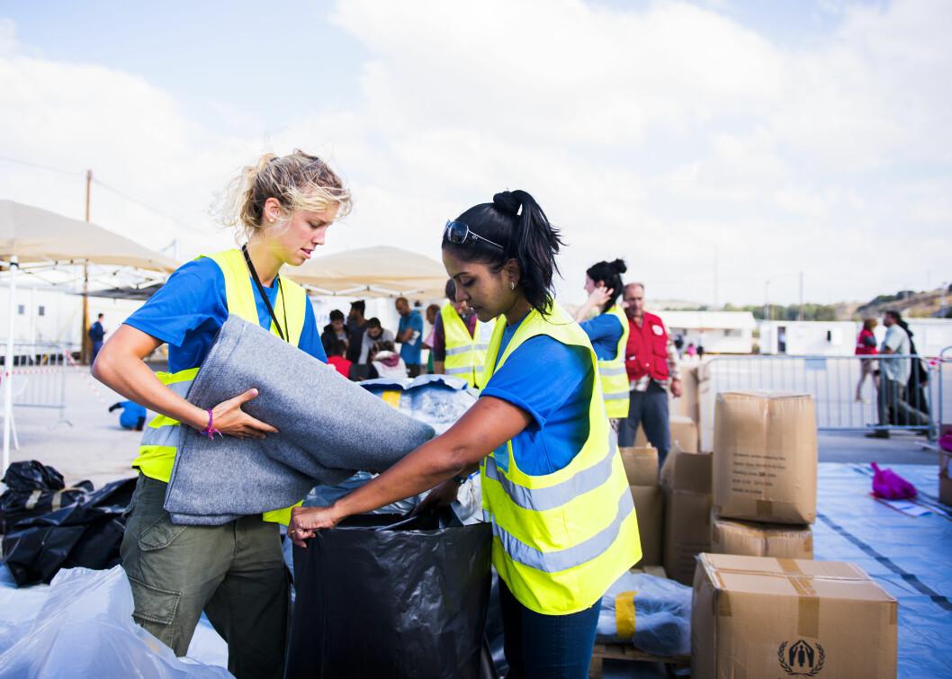 VIKTIG ARBEID: Åsta Marte (t.v.) og noen av Dråpen i Havets frivillige hjelper Røde Kors med utdeling av klær, tepper og soveposer. Foto: Anna Edlund
