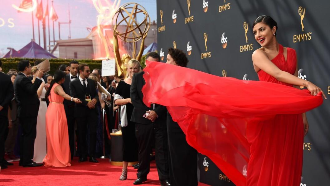 EMMY AWARDS: Priyanka Chopra svinger på den vakre, røde kjolen sin for fotografene. Hun havner på vår best kledde-liste denne gang, sjekk resten lengre ned i saken! Foto: Afp